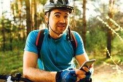 Portrait of young Caucasian cyclist standing in forest, holding mobile phone, using on line application for searching GPS. Coordinates while riding bike. Travel stock image