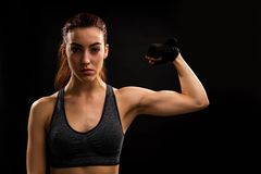 See I My Biceps. Portrait of young Caucasian female athlete flexing muscles while standing against isolated background stock images