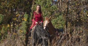 Portrait of young Caucasian female equestrian sitting on back of black horse and holding halter of brown stallion