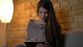Portrait of young caucasian girl sitting on sofa watching into tablet with creativity and interest on cosy home. Background stock video footage