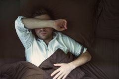 Portrait of a young caucasian man from above sleeping in a dark bed. He is tired after work and sleep in white shirt royalty free stock photo