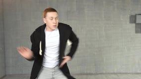 Portrait of young caucasian man dancing in studio. Handsome teen boy performing modern dance moves. Art of hip hop dance stock footage