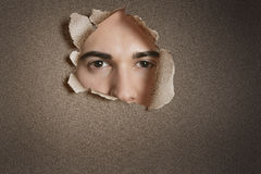 Portrait of a young Caucasian man peeking from ripped paper hole Stock Photo