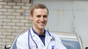 Portrait of young caucasian medical doctor smiling outdoor Stock Image