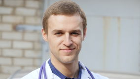 Portrait of young caucasian medical doctor smiling outdoor Stock Photography