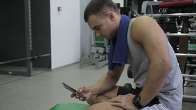 The portrait of young caucasian sportsmen who is resting in the gym scrolling the screen of his cell phone. The athlete is sitting cross-leged on the bench stock footage