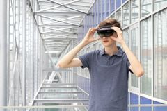 Portrait of young Caucasian teenager using augmented reality HoloLens in modern building. Goggles controlled by various gestures