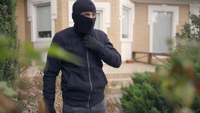 Young caucasian thief in black clothes putting on balaclava before breaking into house. The guy going to steal things in. Portrait of young caucasian thief in stock video footage