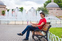 Portrait of young caucasian traveling man reading Stock Image