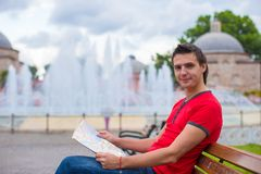 Portrait of young caucasian traveling man reading Royalty Free Stock Images