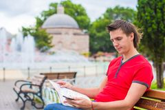 Portrait of young caucasian traveling man reading Stock Images