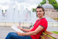 Portrait of young caucasian traveling man reading Stock Photo