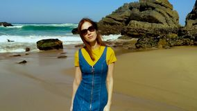 Portrait of young caucasian woman on Atlantic ocean sandy beach Portugal. Portrait of young caucasian woman on Atlantic ocean sandy beach in jeans dress in stock footage