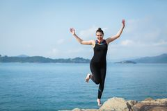 Portrait of young caucasian woman jumping with joy and euphoria at the beach. Selective focus royalty free stock photo