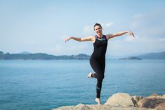 Portrait of young caucasian woman jumping with joy and euphoria. At the beach, selective focus royalty free stock photo
