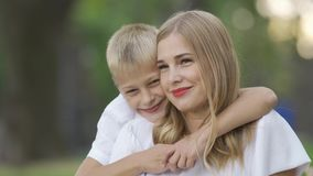 Portrait of young caucasian woman and little boy sitting in the park or forest. Son is hugging his mother. Happy family. Spending time together. Sunny day stock video