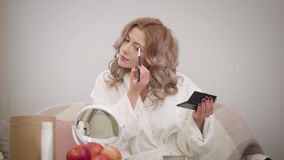 Portrait of young caucasian woman looking at mirror and applying eye shadows. Charming girl in white bathrobe getting. Ready in the morning. Cosmetics, make-up stock video footage
