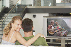Portrait of young Caucasian woman with man watching movie on television in living room Stock Images