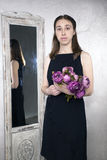 Portrait of a young Caucasian woman with the. Mirror and flower In her hand Royalty Free Stock Image