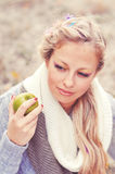 Portrait of young caucasian woman outdoors. Portrait of young caucasian girl holding green apple outdoors Stock Image