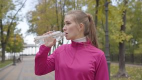 Portrait of a young Caucasian woman in pink sportswear approaching the camera, drinking water and running forward. Confident female runner training in the stock footage