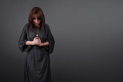 Portrait of a young caucasian woman praying. Prayer girl dressed in Vestments of a nun on gray studio background Royalty Free Stock Images