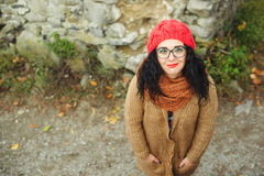 Portrait of young Caucasian woman in red knitted hat outdoors in park. Stock Images