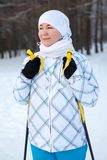 Portrait of young Caucasian woman skier standing on skis with ski poles Stock Photos
