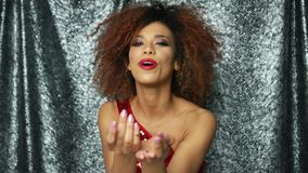 Ethnic woman blowing at confetti. Portrait of young charming ethnic woman looking at camera and blowing on glittering colorful confetti in studio stock video footage