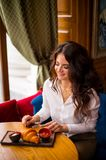 Portrait of charming girl in modern coffee shop at breakfast, nice woman breakfast in cafe eating french croissants. stock image