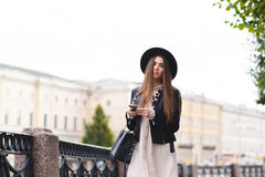 Portrait of young charming female with long beautiful hair holding mobile phone while walking on the street in cloudy day Stock Photo