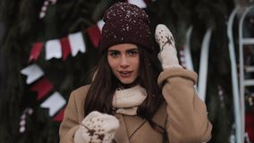 Portrait of young charming girl wearing scarf, mittens, putting her hat straight and smiling, sweeping hair looking to stock video footage