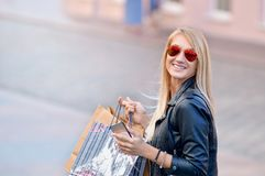 Portrait young charming long-haired woman holding shopping bags stock image