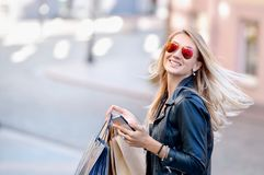 Portrait young charming long-haired woman holding shopping bags royalty free stock photos