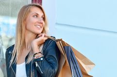 Portrait young charming long-haired woman holding shopping bags royalty free stock image