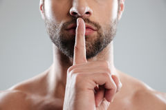 Portrait of a young charming naked man showing silence gesture stock photography