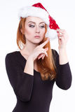Portrait of a young charming red-haired girl in a shiny Christmas hat, she plays with a fluffy white pompom Royalty Free Stock Photo