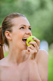 Portrait young charming woman biting apple Royalty Free Stock Photo