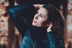 Portrait of a young charming woman in a smoker and scarf against ruins royalty free stock photography