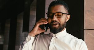 Portrait of the young cheerful african businessman in white shirt and eyeglasses happily talking on the mobile phone stock video footage