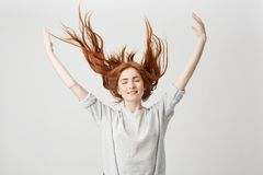 Portrait of young cheerful beautiful redhead girl smiling with closed eyes shaking hair over white background. Stock Photos