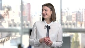 Portrait of young cheerful business woman. Modern brunette lady is smiling on window city background. Happy office manager stock video footage