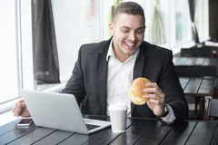 Portrait of young cheerful businessman eating hamburger while wo. Portrait of happy smiling young business man sitting with glass of drink and hamburger in fast Stock Images