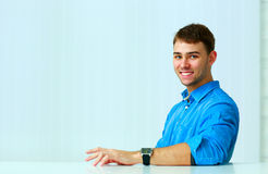 Portrait of a young cheerful businessman sitting at the table Stock Photography