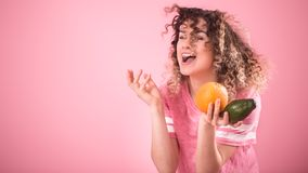 Portrait of a young cheerful girl with curly hair with fruit in her hands royalty free stock photos