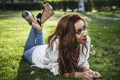 Portrait of young cheerful girl lying on the grass Stock Photo