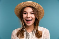 Portrait of a young cheerful girl in summer hat isolated over blue background,. Looking at camera royalty free stock images