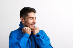 Portrait of a young hispanic man with blue anorak in a studio. Portrait of a young cheerful hispanic man with blue anorak in a studio stock photography