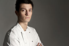 Portrait of a young chef. This is a portrait of a young chef on a grey background royalty free stock photos