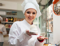 Portrait of young chef. At confectionery display with pastry stock photography